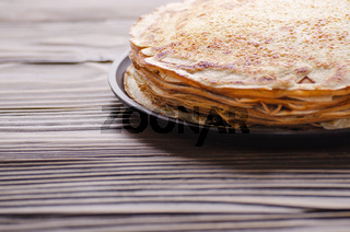 Stack of French crepes in frying pan on wooden kitchen table