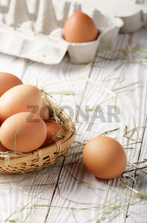 Raw organic brown chicken eggs in square wicker basket on white kitchen wooden table