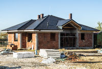 Building a new brick house with black roof. Small houses on construction site.