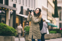 Beautiful young tourist woman stands on the background of the central street in Munich in Germany in winter. Holds a black big professional camera, takes a photo and smiles