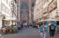 view of the Strasbourg Cathedral and many tourists on the Rue Merciere street in high summer