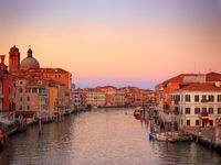 the grand canal in venice in glowing evening twilight with sunset sky with reflections of historic buildings and boats