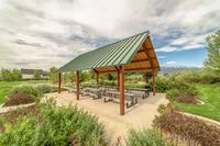 Picnic pavilion at a park with view of distant mountain and cloudy blue sky
