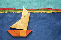 tangram sailboat over abstract paper landscape