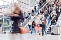 Geschäftsleute auf Rolltreppe bei Business Messe