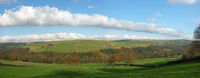 wide panoramic view of west yorkshire countryside with the forest of hardcastle crags in the bottom of a wide valley surrounded by meadows with grazing sheep in bright autumn sunshine