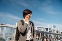 Young man talking on smartphone outdoors. Communication concept. Front view.