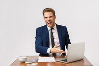 What the hell is that, its really bad. Bothered, outraged young boss, businessman in formal suit, sitting office desk, pointing laptop display complaining diagram, standing white background