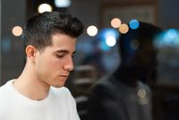 Young man with serious expression waiting disappointed at coffee shop in the night.