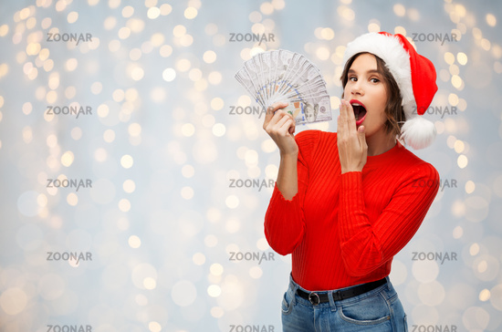 surprised woman in santa hat with money
