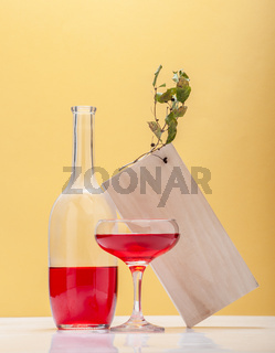 A glass and a glass bottle with a red drink on a yellow background. Art composition.