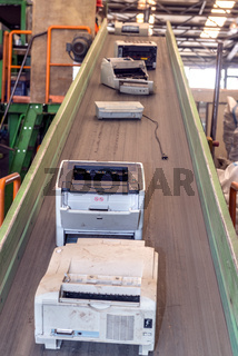 Used office printing machines on an escalator, ready to be disassembled for recycling, inside a recycling plant
