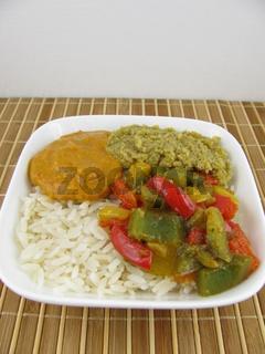 Gekochter Reis mit Olivenpaste und gekochtem bunten Paprika
