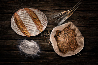 Still life with baking rye bread, ears, flour and bag of grains in a sackcloth