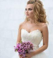 Gorgeous young bride with nice bouquet in studio