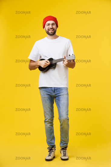 Guitarist man plays on the electric guitar with bright emotions, isolated on yellow background.