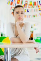 young beautiful woman in white dress sits at a table in the cafe