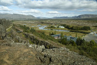 Panoramic Scenic View On A Winding River, Valley, Farmhouses And Mountains In Iceland