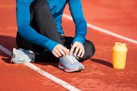 Close up view, of an athlete tying his shoe laces. Man tightening his shoe laces sitting on the ground on a running track.