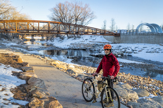 senior male cyclist is riding a bike in winter sunset scenery