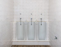 Three full length urinals in a row on a tiled bathroom or restroom wall