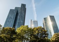 Commerzbank, deutsche Bahn and other Skyscraper low angle with trees in forefront on a sunny day in frankfurt, hessen, germany