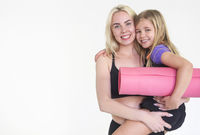 Mother and daughter holding yoga mats, isolated on white