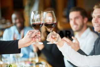 Freunde feiern und stoßen an mit Rotwein