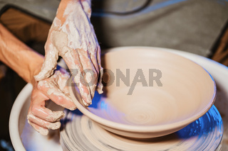 Experienced potter shapes the clay product - plate - with pottery tools. Close up of male hands working on potter's wheel. Shot of half-finished ceramic plate spinning on jigger