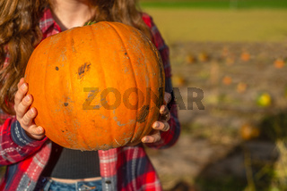 Close Up of a Young Woman Holding a Pumpkin in a Pumkin Patch