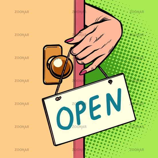 open woman hand hangs a sign on the door