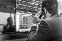 Stock trader looking at market data on computer screens.