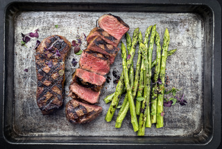 Traditional barbecue dry aged sliced roast beef steak with green asparagus as top view on an old backing form