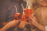 Group of friends cheers with aperol spritz in restaurant