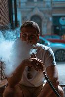 Silhouette of hookah maker blowing smoke in the dark.