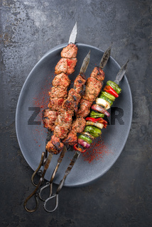 Traditional Russian shashlik on a barbecue skewer with vegetable and onion as top view on a modern design cast iron plate with copy space