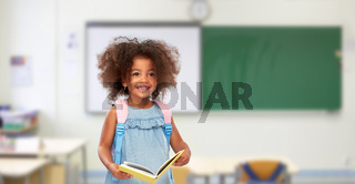 happy little african girl with book and backpack