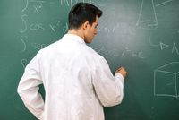 College student in laboratory class, with white coat , writing on chalkboard.