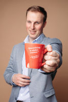 Successful businessman with cup with reassuring slogan.