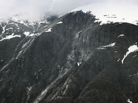 Steep Glacially Polished Cliffs And Mountain Peak Covered With Snow And Clouds, Alaska
