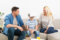 Happy family at home on living room sofa having fun playing games using virtual reality headset