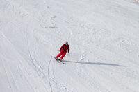 Skier on snowy sunlit ski slope at winter