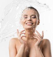 Pretty girl enjoying water splash studio shot