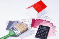Haus mit Taschenrechner, Pinsel und Farbfächer auf Tastatur