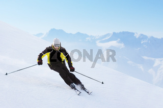 Alpine skier on piste running downhill