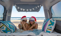 Two girls traveling celebrate Christmas by the beach in summer