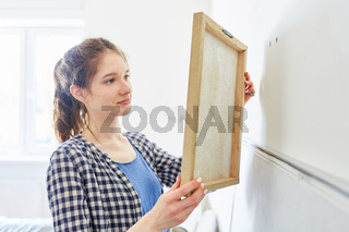 Junge Frau hängt ein Bild an der Wand auf