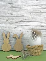 Ostern Hintergrund mit Osterei, Osterhasen und Schmetterling auf grün vor Holz