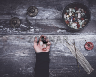 Hand holding small stones in energy healing  meditation on rustic wooden table with burning incense