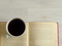 a cup of coffee and an open book on white wooden background.
